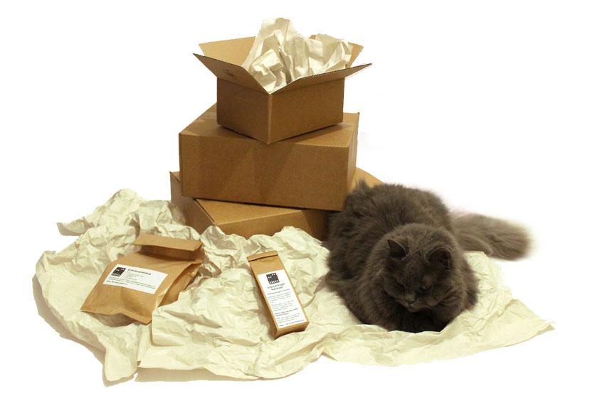 kätts-Chefkatze Felina präsentiert das gesamte Verpackungsortiment von kätts: Kartons, Papiertüten und Papierbögen zum Ausstopfen.